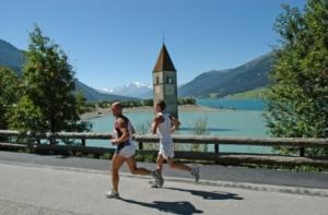 Die Laufstrecke führt vorbei am Wahrzeichen des Reschensees – dem fast versunkenen Kirchturm von Graun im Vinschgau. Bildnachweis: Gerald Burger
