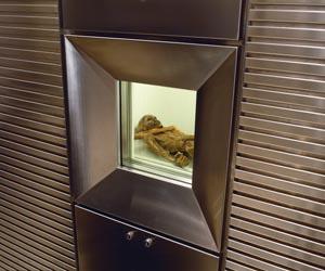 Für den Mann aus dem Eis wurde ein weltweit einzigartiges Kühlsystem entwickelt, das es erlaubt, die Mumie der Öffentlichkeit zu zeigen. Um den Feuchtigkeitsverlust des Ötzi zu verhindern, wird sie mit Wasser bespritzt, so dass sich an der Oberfläche eine feine Eisschicht bildet. Das Bild zeigt das Vitrinenfenster zur Kühlzelle der Mumie. - Foto: Südtiroler Archäologiemuseum
